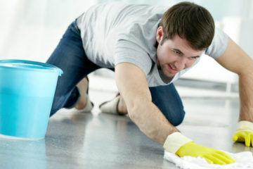 Young man washing floor in protective gloves