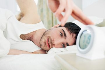 man-in-bed-turning-off-alarm-clock